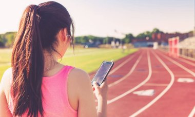 Female athlete listening to music on a running track