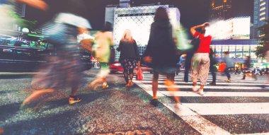 Motion blurred people walking at night
