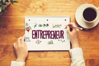Entrepreneur text with a person holding a pen