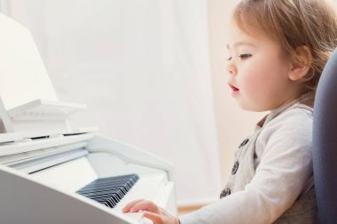 Toddler girl learning to play piano