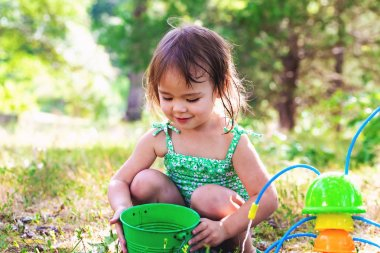 Happy toddler girl playing with water