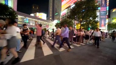 People cross the famous intersection in Shibuya, Tokyo, Japan