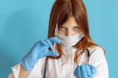 Egy tinédzser lány orvososdit játszik, egy fogalmat, hogy szakmát válasszon egy gyereknek, egy vörös hajú lányt fehér ingben, védőmaszkban és fonendoszkóppal a kezében.