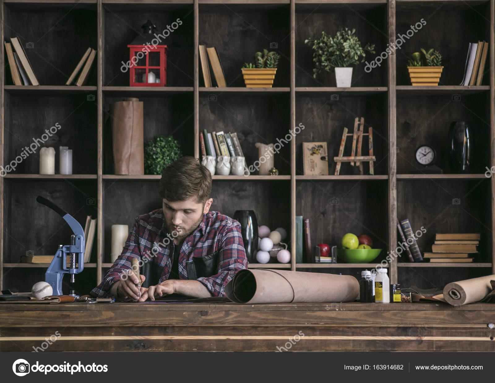 Τακτοποιημένη εργασία με το εργαλείο. Νεαρός άνδρας δερμάτινων ειδών  κατασκευαστής κάθεται στο ξύλινο τραπέζι και τη χρήση του awl να κάνει κοπή  δέρμα στο ... c6ce4b46b91