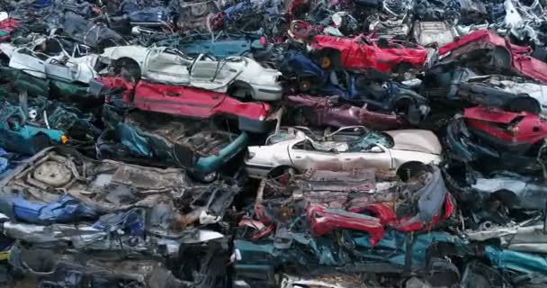 Crushed corroded old cars stacked in scrapyard.