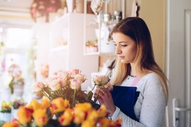 Young woman owner of florist shop making a composition of pink roses.