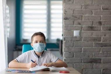Child in protective medical mask doing his homework. School closed during coronavirus