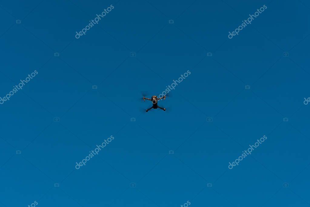 Drone flies in a blue sky