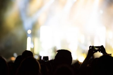 Raised arms holding smart phones to recording a live concert