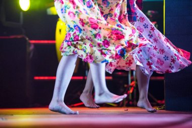 Young dancer woman barefoot in gypsy dress dancing on stage