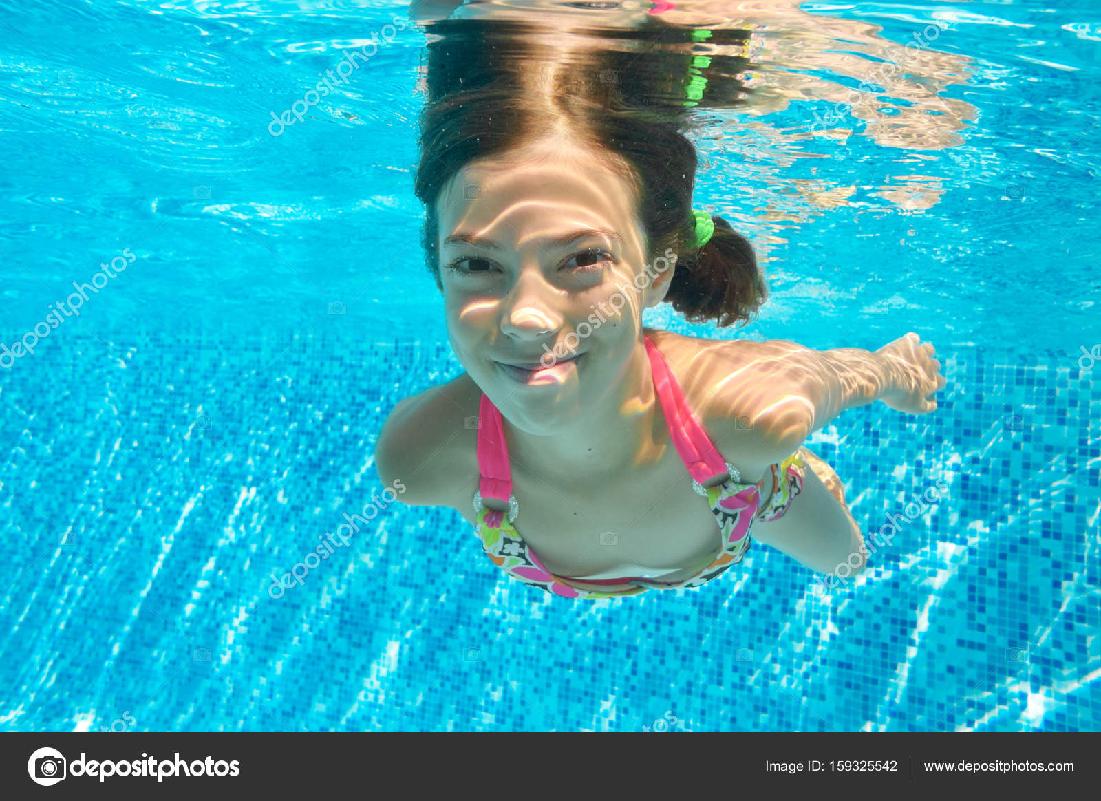 Child swims in pool underwater, happy active girl dives