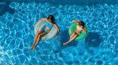 Letecký horní pohled dětí v bazénu shora, šťastné děti plavat na nafukovací prstenec koblihy a bavit se ve vodě na rodinnou dovolenou