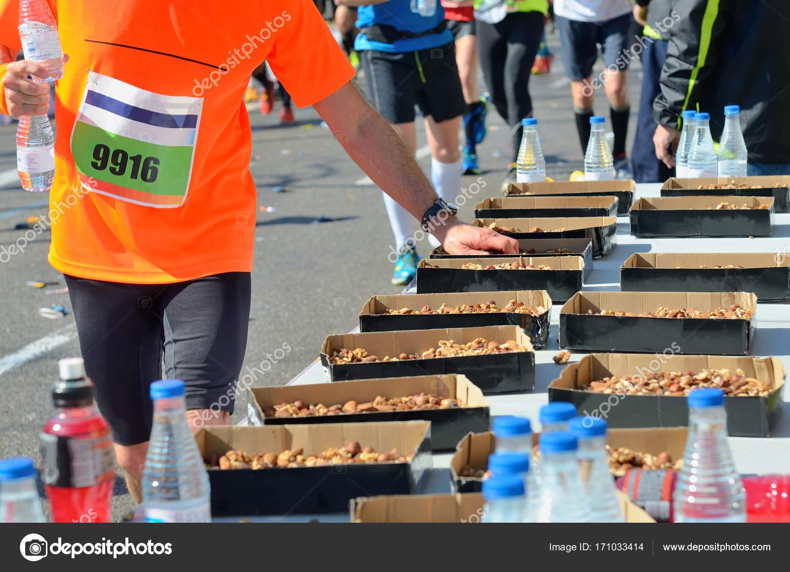 Marathon hand Läufer Straße Rennen, Nahrungsaufnahme und Getränke am ...