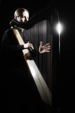 Harp player. Harpist playing Irish harp isolated on black