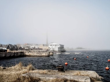 Abandoned concrete floaing sea fish fatory in fog
