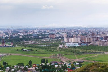 View of the city from the mountain. Summer landscape. Kyrgyzstan, Bishkek. Buildings and architecture