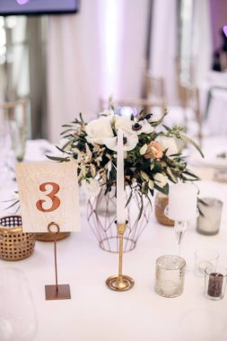 White wedding table decorated with flowers and eucalyptus, plates, glasses