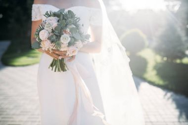 bride's hands with wedding bouquet with eucalyptus