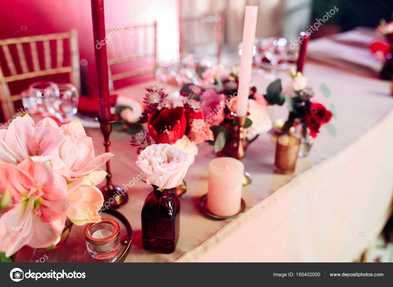Decorated area in gold and burgundy colors with white candles and ...