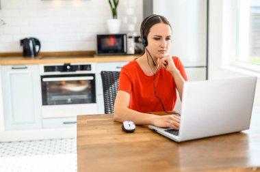 Genç kadın kulaklık ve dizüstü bilgisayar kullanarak evden çalışıyor.