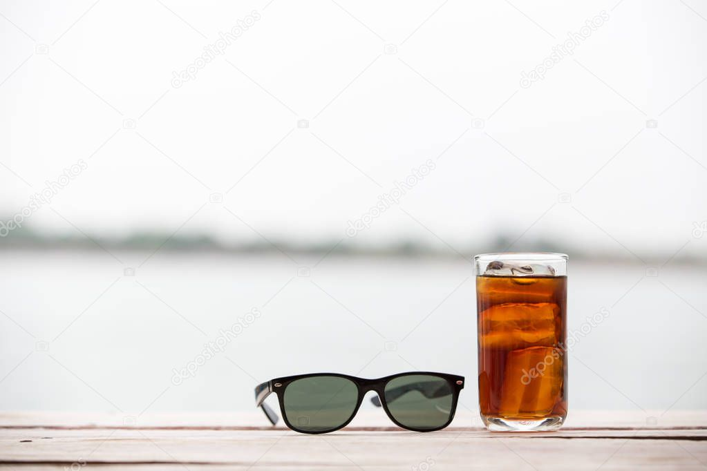 A glass of water with black glasses placed on a wooden plate.