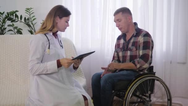 Sozialarbeiter, behinderter Mann im Rollstuhl spricht während einer Untersuchung im Haus mit Krankenschwester über seine gesundheitlichen Probleme