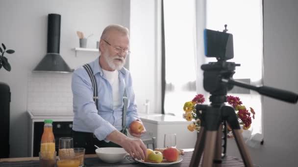 egészséges ételek, egy szakállas és látásjavító szemüveges idős férfi megfelelő táplálkozást javasol, és különböző gabonaféléket mutat be az asztalnál a konyhában.