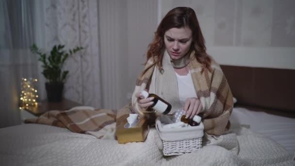 krankes Mädchen mit Temperatur nimmt Tabletten, während sie mit einer warmen Decke auf dem Sofa sitzt, junge Frau fühlt sich während der Grippe oder Fieber zu Hause schlecht