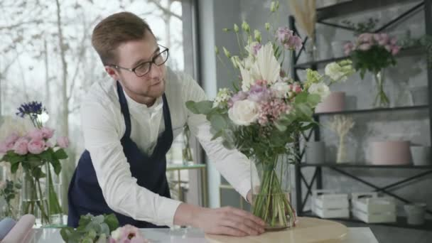 portrait of representative of gender work professional florist attractive man collects beautiful bouquet of flowers for sale in flower shop, small business concept
