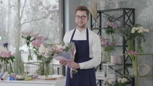 portrét usmívajícího se atraktivního chlapce reprezentujícího pohlaví profese květinářství s kyticí květin pracuje v květinářství, úspěšné podnikání
