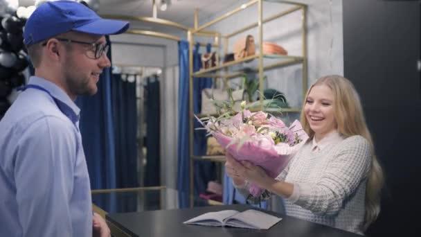dodávka, muž pracující v doručovací službě přináší kytice klientovi na pracovišti, mladá atraktivní dívka dostává balíček v podobě květin