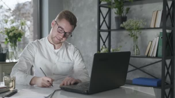 young male entrepreneur working at computer conducts business online happy from work done, asking and sitting on table in modern office with beautiful interior