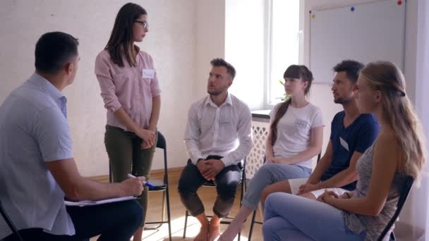 group therapy, girl talking about problems and sharing emotions standing in front of people
