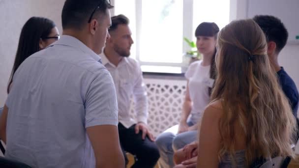 podpora a pomoc, muži a ženy sedí v kruhu dát pět společně na skupinové psychoterapii