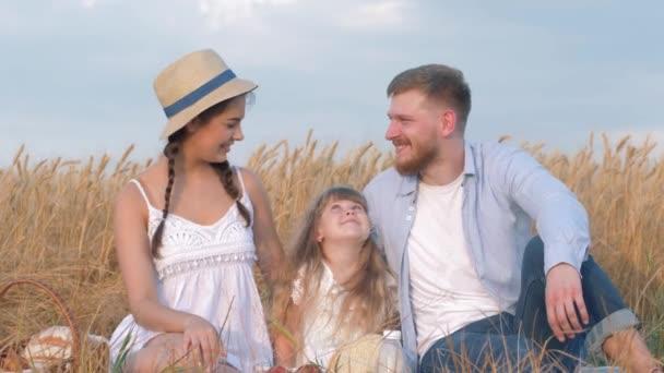idylický rodinný portrét, šťastný mladý pár sedí v blízkosti své holčičky a dívá se na sebe s úsměvem na venkovním pikniku v obilí ječmene pole v době sklizně