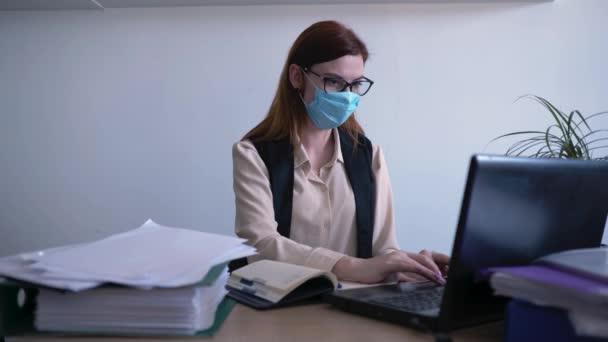 karantén, a rossz egészségi állapotban lévő női alkalmazott orvosi maszkot használ a vírus és a fertőzés elleni védelemre, miközben távoli irodában, az egészségügyi ellátásban dolgozik a számítógépen.