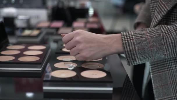 közelkép női kéz, női vásárló teszteli arc kozmetikumok professzionális boltban, bevásárló lány választott smink por a boltban