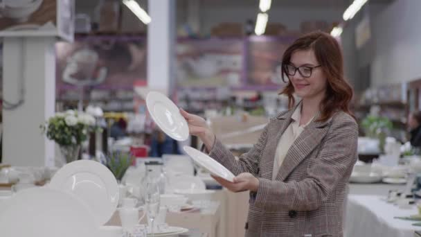 portrét mladé usměvavé ženy nakupující v brýlích pro vidění vybírající stolní nádobí pro soupravu nádobí na policích domácího obchodu