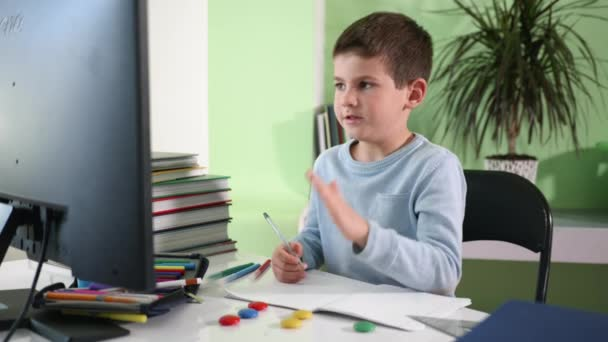 home schooling, handsome smart boy teaches home lessons sitting at a computer and watching a video lesson on a monitor screen