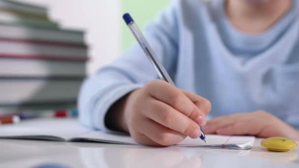 iskolai kellékek, iskolás fiú házi feladatot ír egy jegyzetfüzetbe, a háttérben tollak, könyvek és jegyzetfüzetek, kezek közelről