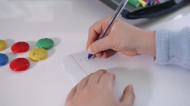 fiú csinál házi feladatot ír egy jegyzetfüzetben a háttér-ból iskolai kellékek ül egy asztalnál, kezét közelkép