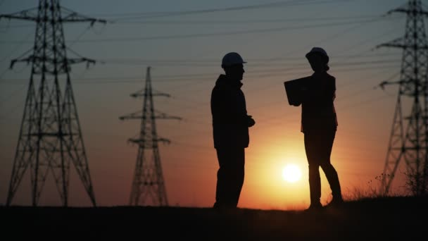 Ingenieure Frau und Mann mit Laptop und Zeichnungen diskutieren Plan für die Stromversorgung der Stadt Hintergrund des Kraftwerks und Sonnenuntergang, Silhouette