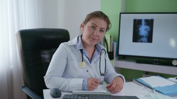 junge Ärztin mit Phonendoskop in weißem Arztkittel kommuniziert mit Patientin per Videolink und konsultiert Patientenhintergrund des Monitors mit einem Röntgenbild