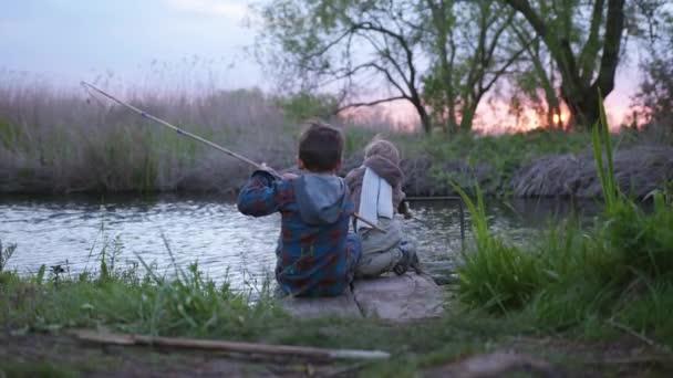 malý rybář, děti bratři sedí na molu a ryby s rybářským prutem v řece při západu slunce venku uprostřed hole, pohled zezadu