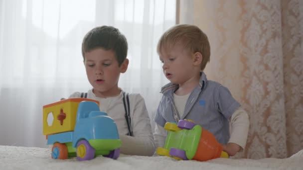 vzdělávací hračky, malí roztomilí chlapci, bratři rozvíjet své tvůrčí myšlení tím, že hraje s bezpečnými plastovými auty na pokoji