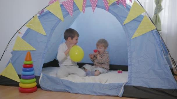 domácí zábava, roztomilí veselí kluci bavte se a užijte si hry doma foukání balónky