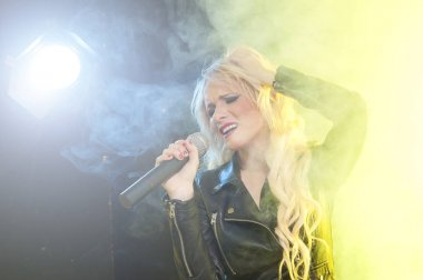 Portrait of a charming blonde woman singing with microphone