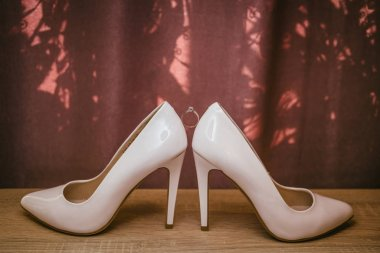 Gold diamond ring between pair of white high heel shoes. Wedding details on red background
