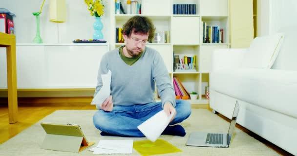 Muž kontroluje účty a daně doma s tabletu a pc