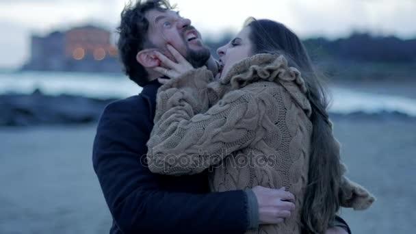hungrige schöne weibliche Vampir versucht, verängstigte Mann am Strand Zeitlupe beißen.